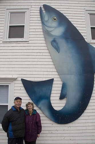Russ and Carol Hazelden stand next to fish mural on the side of their house in Dover East.